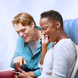 Couple sharing earbuds and watching content on a tablet inflight